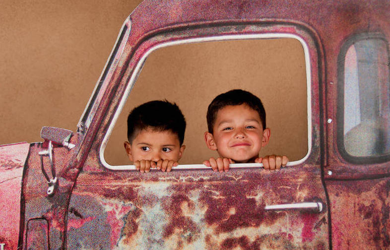 Two boys in antique pickup truck